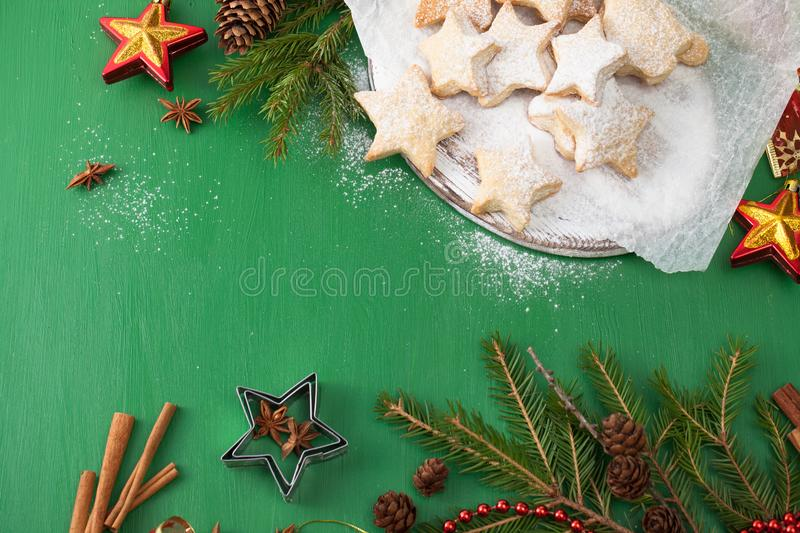 Cookies dusted with powdered sugar with Christmas decorations on green stock illustration