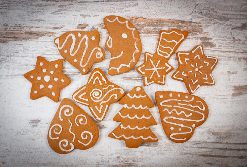 Fresh baked decorated gingerbread on old wooden background, christmas time stock photos