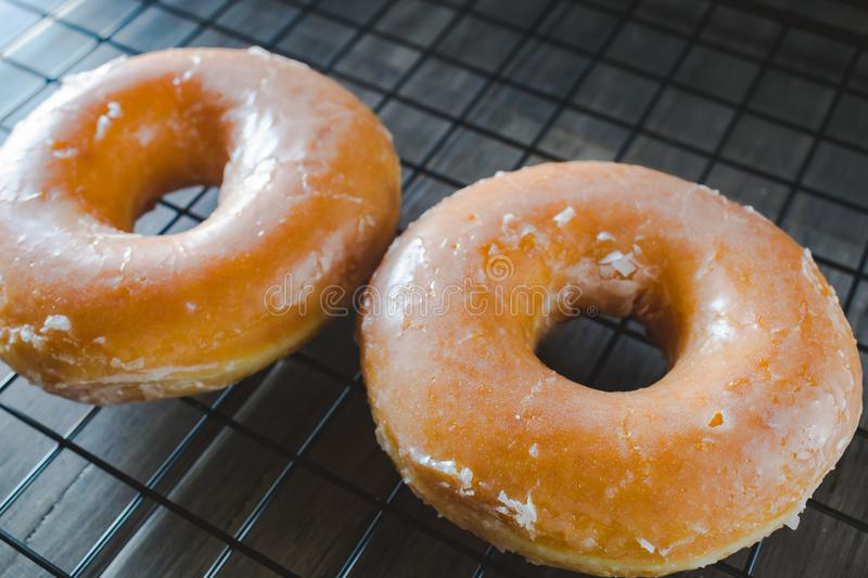 Glazed Donuts. Fresh baked glazed donuts cooling on a wire grid rack royalty free stock image