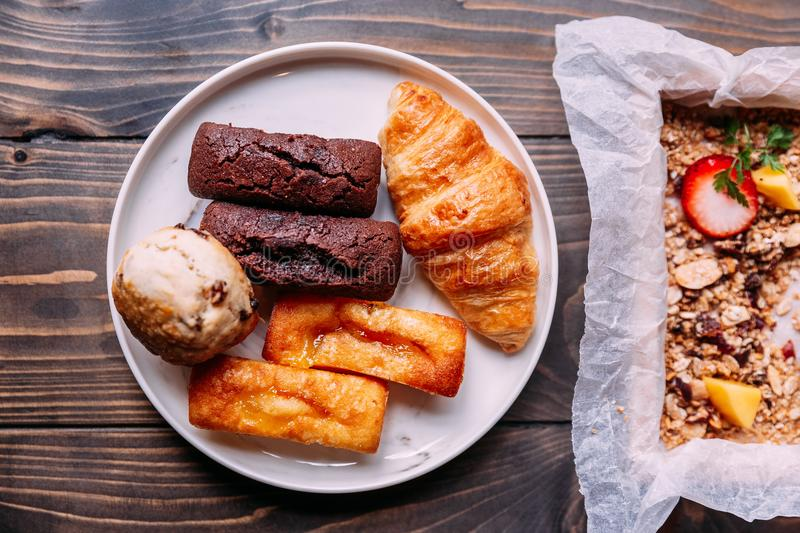 Fresh baked goods on white dish including scone, croissant, financier and chocolate financier.  stock images
