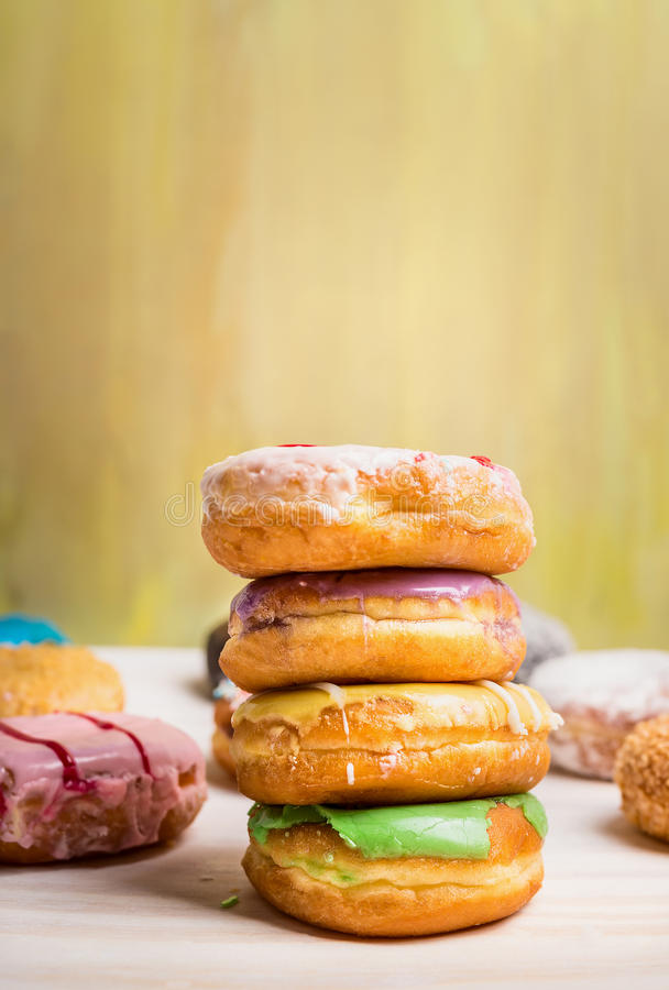 Fresh baked homemade colorful donuts on light wooden stock photo