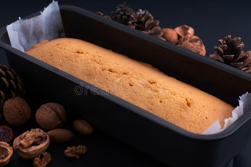 Fresh baked homemade pound, butter cake in loaf pan on slate stone plate decor by pinecorn and walnuts stock photography