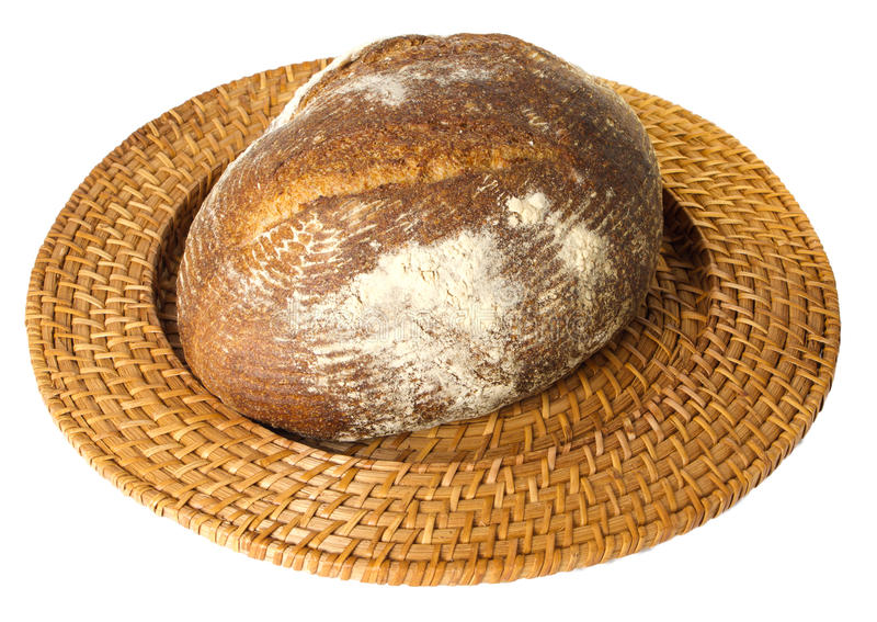 Fresh baked loaf of sourdough rye bread. Displayed on wicker tray isolated on white stock photos
