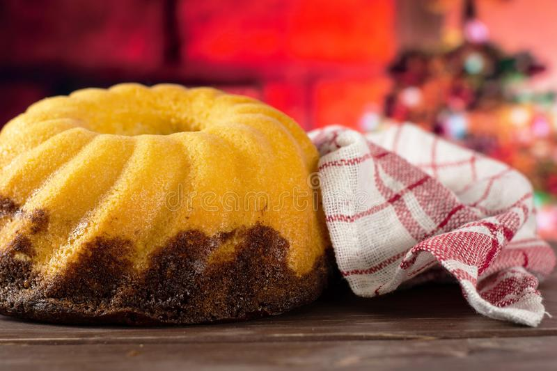 Fresh baked marble gugelhupf sweet bread with christmas tree behind. One whole fresh baked marble gugelhupf sweet bread variety with a tea towel with christmas stock photography