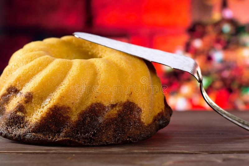 Fresh baked marble gugelhupf sweet bread with christmas tree behind stock photo
