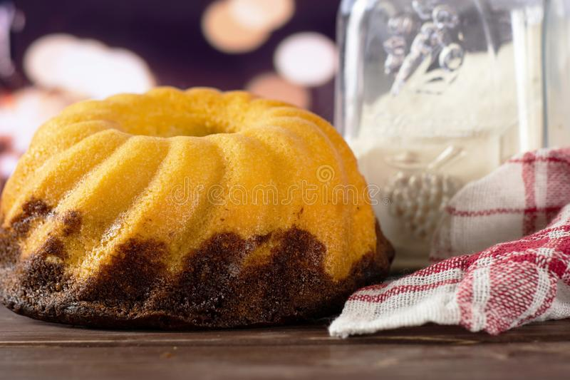Fresh baked marble gugelhupf sweet bread with lights. One whole fresh baked marble gugelhupf sweet bread variety with a can of flour and a tea towel with lights royalty free stock photography