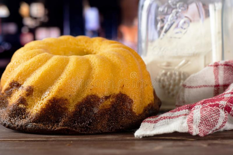 Fresh baked marble gugelhupf sweet bread with restaurant. One whole fresh baked marble gugelhupf sweet bread variety with a can of flour and a tea towel with royalty free stock photography