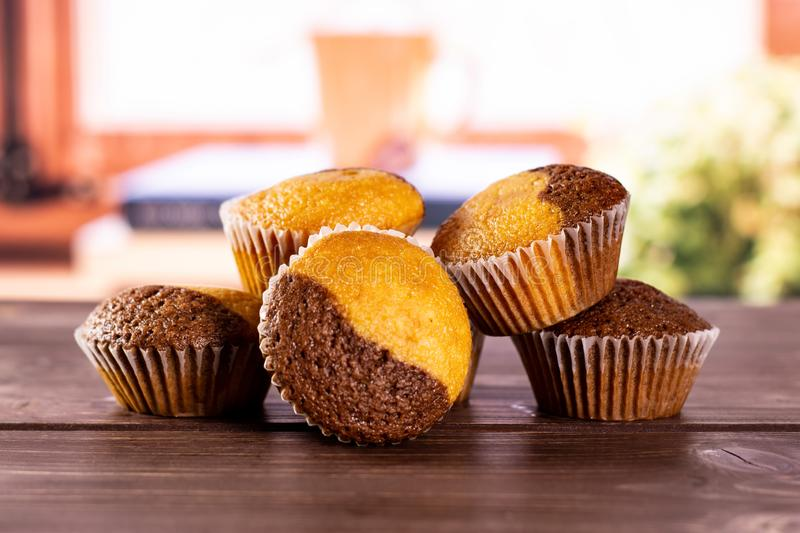 Fresh baked marble muffin with books on window. Group of five whole fresh baked marble muffin with books near the window in background royalty free stock image