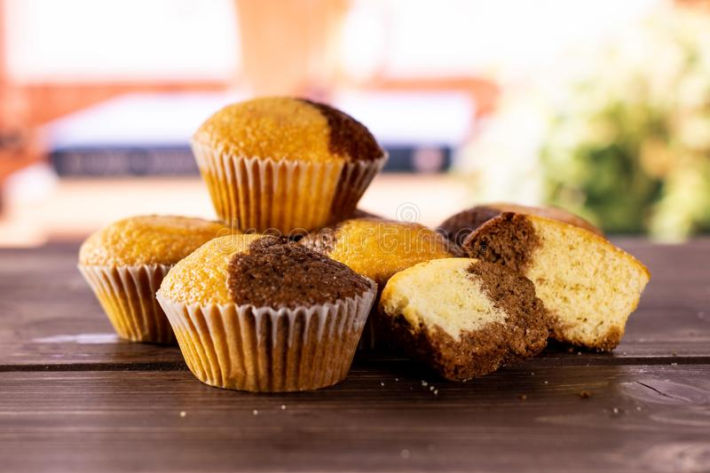 Fresh baked marble muffin with books on window. Group of four whole two halves of fresh baked marble muffin with books near the window in background stock photos