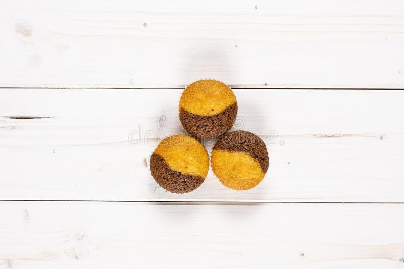 Fresh baked marble muffin on grey wood. Group of three whole fresh baked marble muffin flatlay on white wood stock image