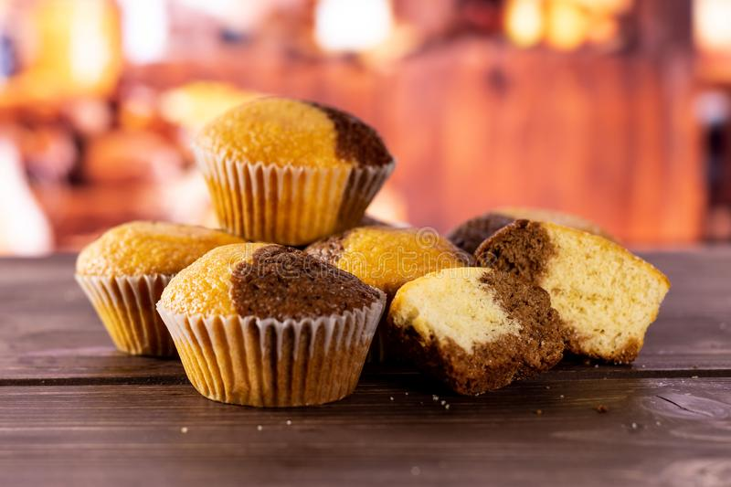 Fresh baked marble muffin with rustic kitchen. Group of four whole two halves of fresh baked marble muffin with rustic wood kitchen in background royalty free stock photo
