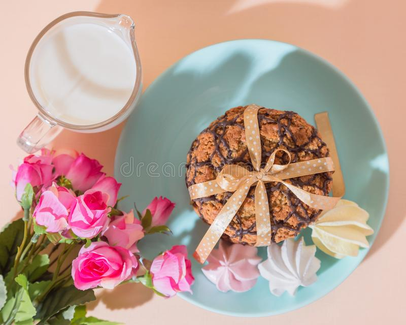 Fresh baked oatmeal crispy cookies on a blue plate on a background of peach color, milk, French multi-colored meringues. Delicious royalty free stock images