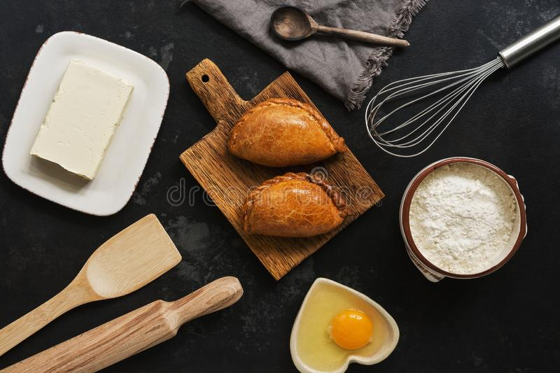 Fresh baked pasties and baking ingredients on a dark stone background. Russian pirozhki. Top view stock photography