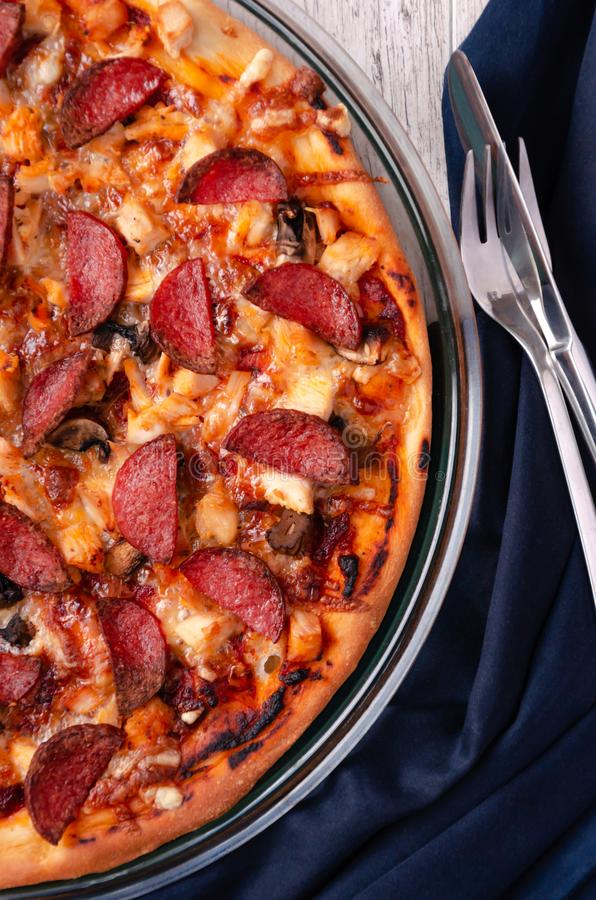 Fresh baked pepperoni pizza on a wooden surface royalty free stock photography