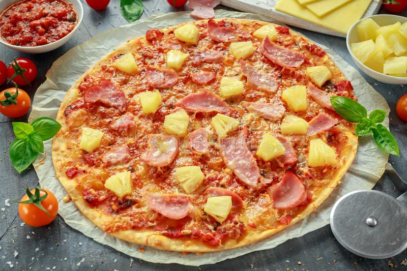 Fresh baked pizza hawaii with ham and pineapple, basil, tomatoes on backed paper.  royalty free stock photo