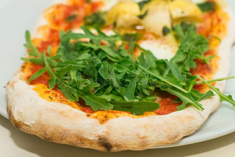 Fresh baked pizza with melted cheese, Italian herbs and tomato sauce and fresh basil on a white plate. Italian food, menu, restaur royalty free stock photos