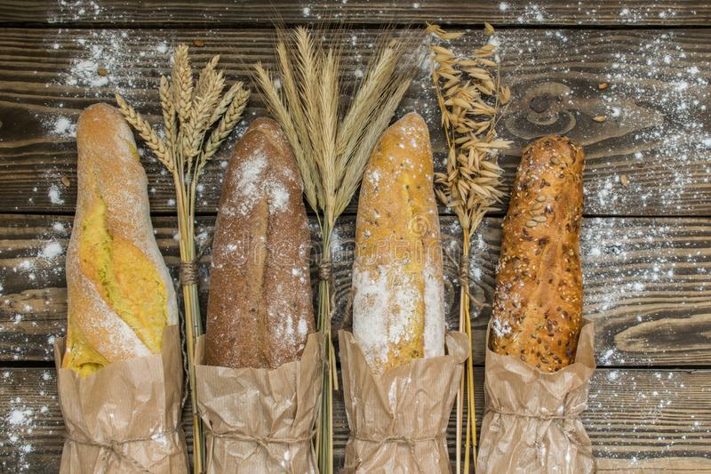 Fresh baked rustic bread loaves in paper bags on dark wood background royalty free stock image