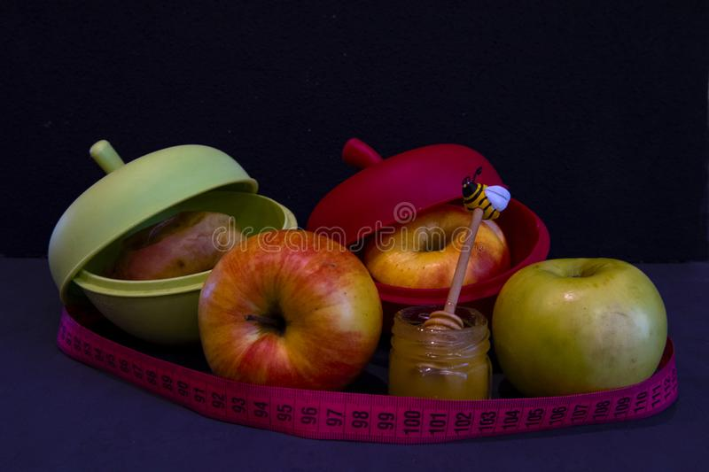 Fresh and baked in a special silicone form apples. Next to a jar of honey with a spoon inside and with a centimeter around royalty free stock images