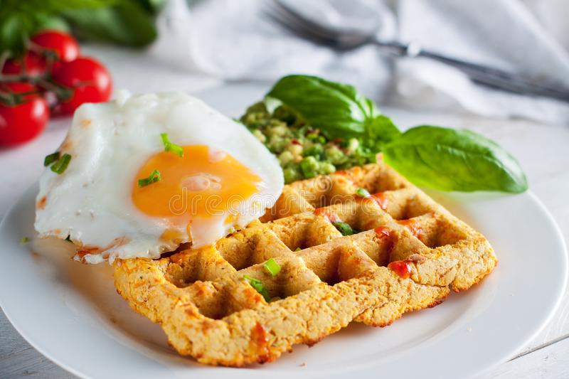 Sweet potato waffles with eggs. Fresh baked sweet potato waffles with scrambled eggs and avocado dip. Healthy breakfast royalty free stock images