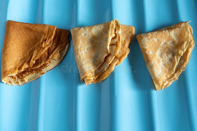 fresh baked thin pancake on blue background. food and baking stock image