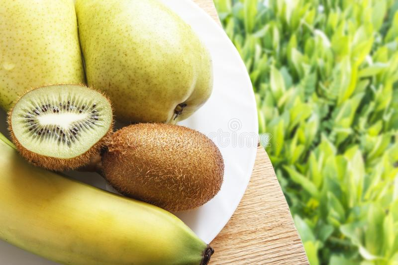 Fresh banana, pear and kiwi for healthy dietary breakfast on wooden table and on green grasses background. Natural organic ripe fr. Uits. Top view with copy stock image