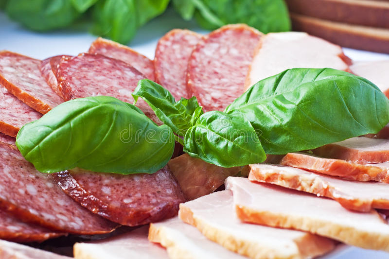 Fresh basil on a cutting sausage background stock photography