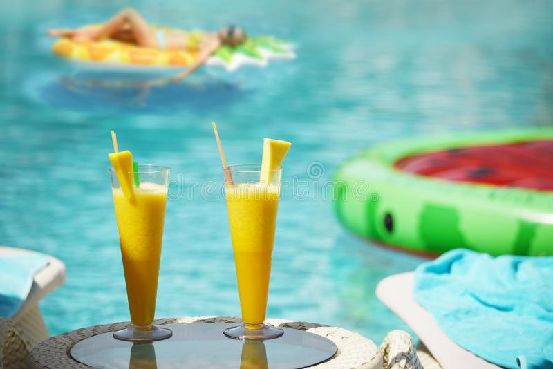 Fresh bass citrus juices. Girl on an air mattress in the background in the pool water. The atmosphere of a holiday by the pool. royalty free stock photos