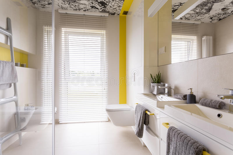 Fresh bathroom with yellow decor. Fresh and bright contemporary bathroom with beige tiles, mirror, graphic ceiling, double sink, toilet, yellow decor and window stock images