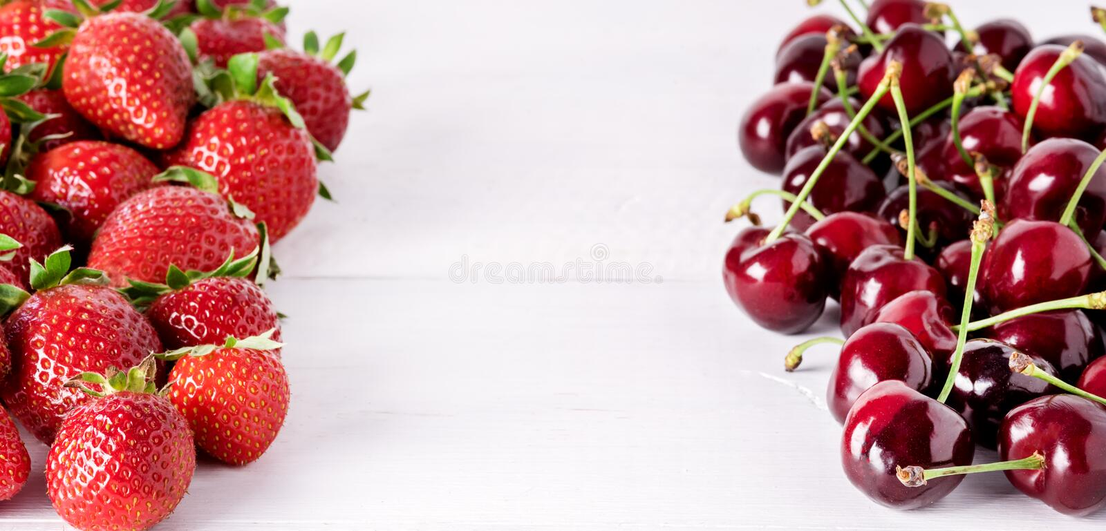 Fresh Beautiful Ripe Berries on a White Wooden Background Sweet Strawberries and Cherry Frame Long stock photos