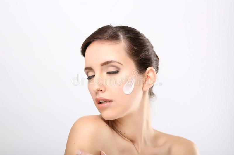 Fresh beautiful young adult woman. Applying moisturiser cream on her face royalty free stock photos
