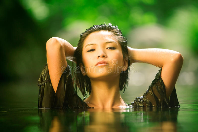 Fresh beauty. Beautiful Asian girl rises up out of stream