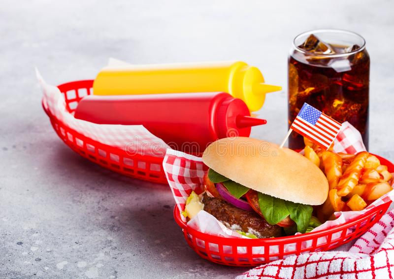 Fresh beef burger with sauce and vegetables and glass of cola soft drink with potato chips fries in red serving basket on stone ki stock image