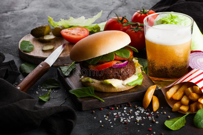Fresh beef burger with sauce and vegetables and glass of craft lager beer with potato chips fries on stone kitchen table backgroun stock photography