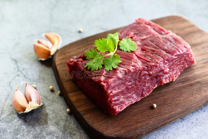 Fresh beef piece for steak or grilled barbecue / Raw meat beef steak with spices garlic on wooden cutting board and black royalty free stock photos