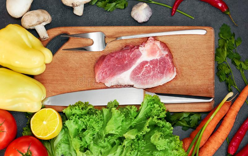 Fresh beef steak, wooden spoon, Assortment of Fresh Vegetables, aromatic herbs, spices and vegetables for cooking royalty free stock photos