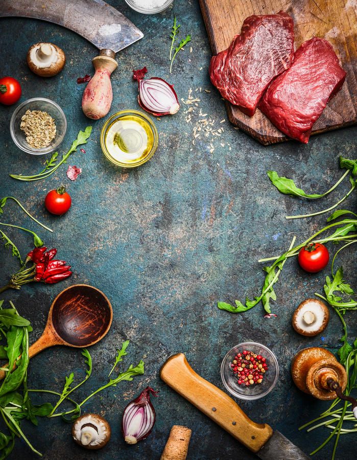 Fresh beef steak, wooden spoon, knife and aromatic herbs, spices and vegetables for cooking , on rustic background, top view stock photo