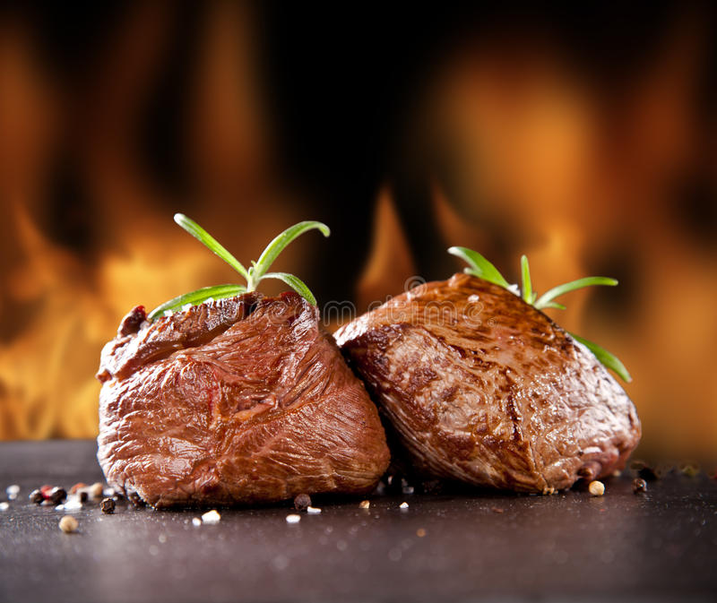 Fresh beef steaks on black stone and fire. Pieces of red meat steaks with rosemary served on black stone surface. Blur fire flames on background royalty free stock photography