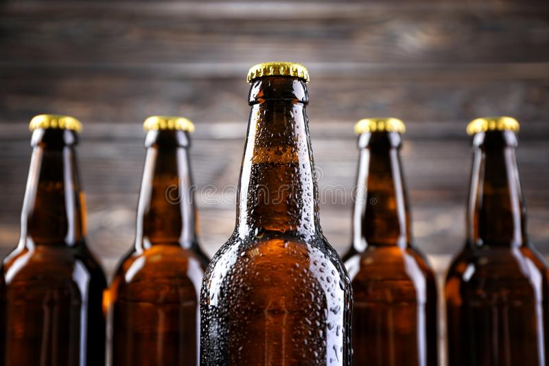 Fresh beer in glass bottles. On blurred background, closeup stock photos