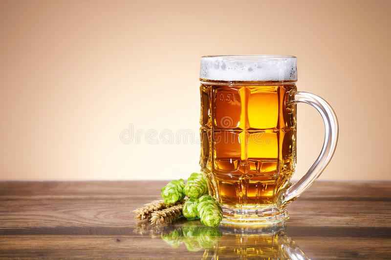 Fresh beer in a mug. A glass of beer with a fresh, foamy beer in a glass mug, ears of wheat, ripe fruit hops, brewing ingredients, a wooden table royalty free stock images
