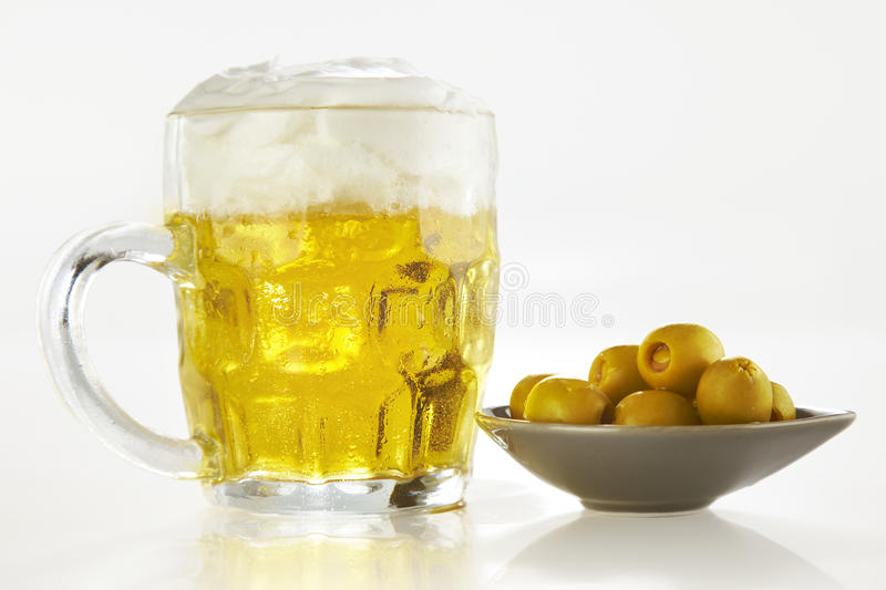 Fresh beer and olives over white background royalty free stock image