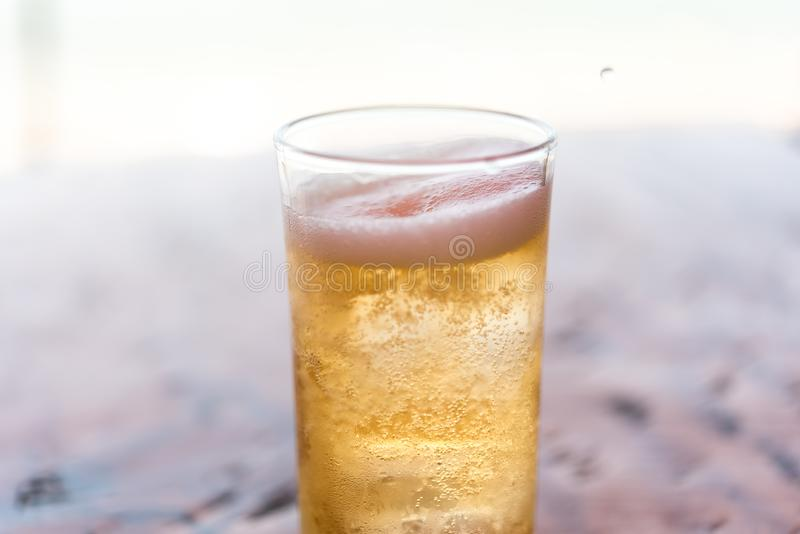 Fresh beer water in to glass with ice and froth royalty free stock photography
