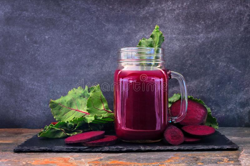 Beet juice in a mason jar on a slate platter over a dark background. Fresh beet juice in a mason jar glass on a slate platter over a dark background stock photos