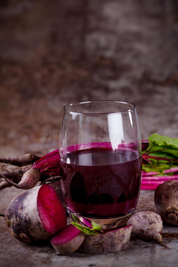 Fresh beetroot juice. Glass with fresh beetroots juice, with roots, beet leaves in background with rusty metal royalty free stock photo