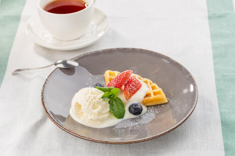 Fresh belgian waffles with ice cream and berries and cup of tea served on the table royalty free stock image