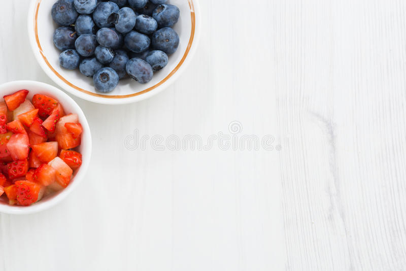 Fresh berries - blueberries and sliced strawberries on white royalty free stock photo
