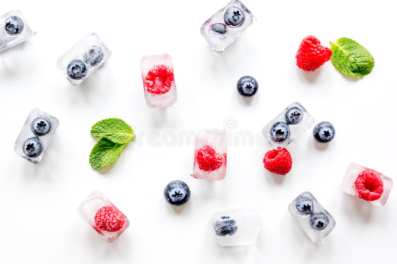 Fresh berries with mint in ice cubes on white background top view royalty free stock image
