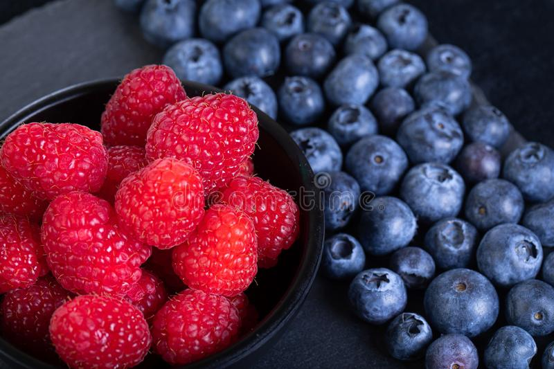 Fresh blueberries and raspberries. Fresh rasberries and blueberries on black stone plate stock photos