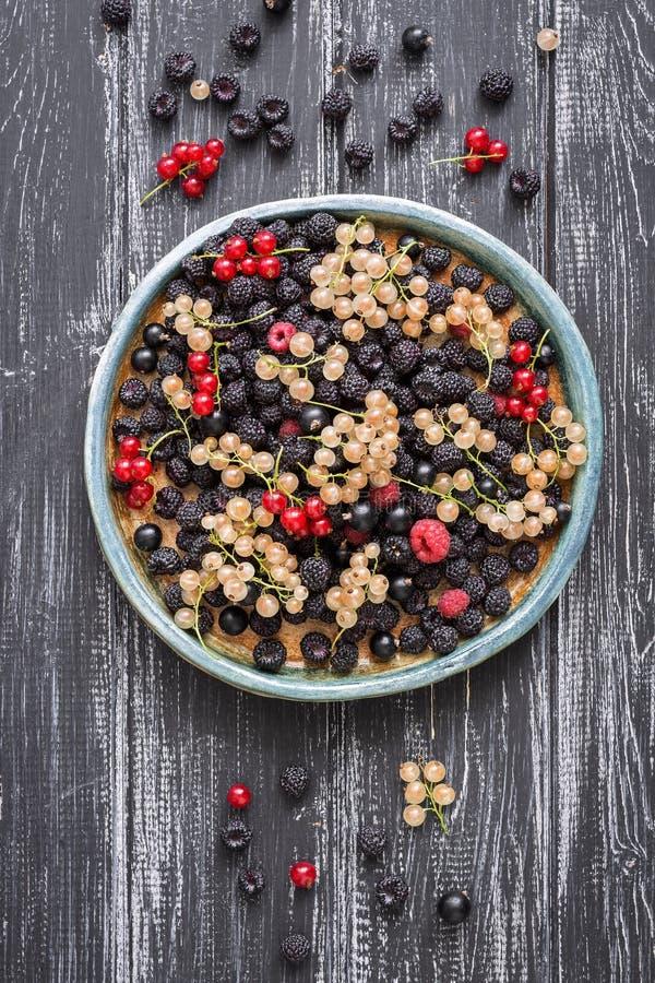 Fresh berries-raspberries,black raspberries, currants on a ceramic dish, rustic wooden dark background. Overhead, top view, flat l. Fresh berries-raspberries royalty free stock image