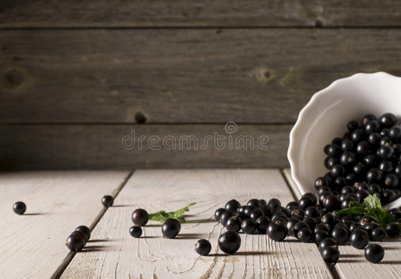 Fresh berries raspberry, red currant, black currant in glass bowl on wooden table stock photography