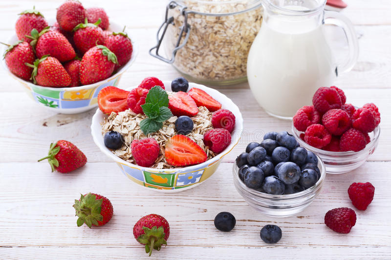 Fresh berries strawberry, raspberries and natural flakes for breakfast, Woman pouring milk into bowl with muesli top stock image